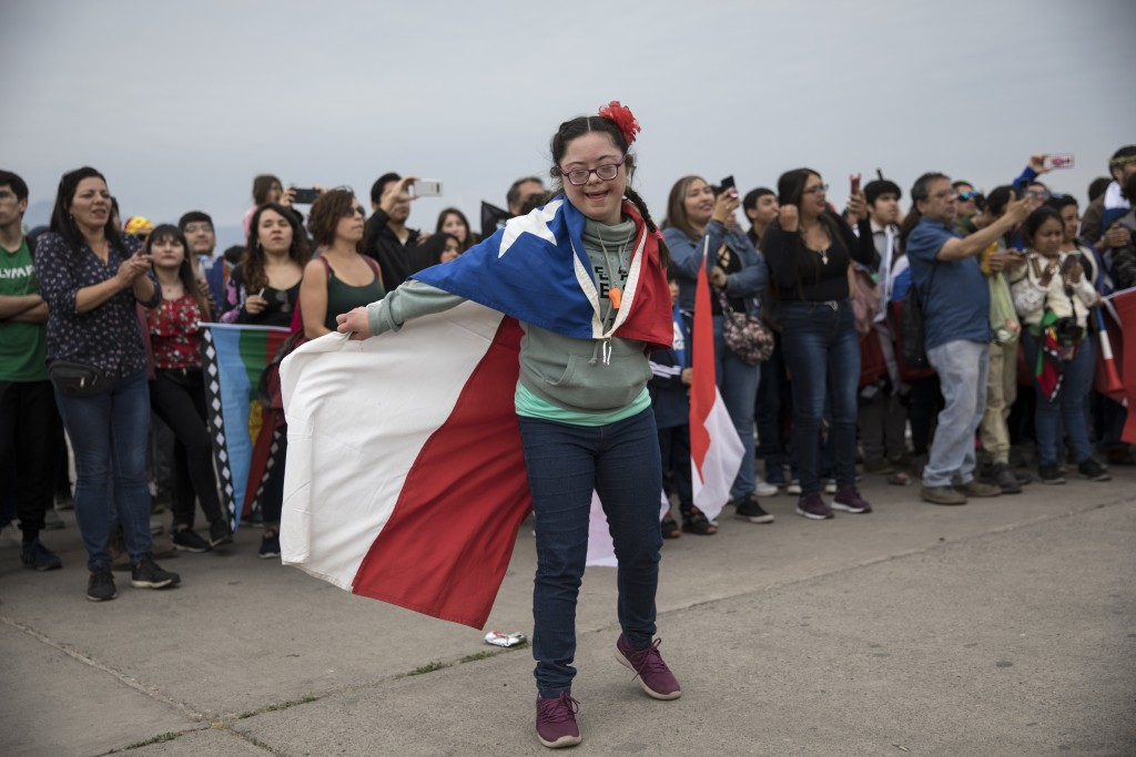 A girl draped with a Chilean flag dances in O'Higgins Park during an anti-government music concert in Santiago, Chile, Sunday, Oct. 27, 2019. Days of ...