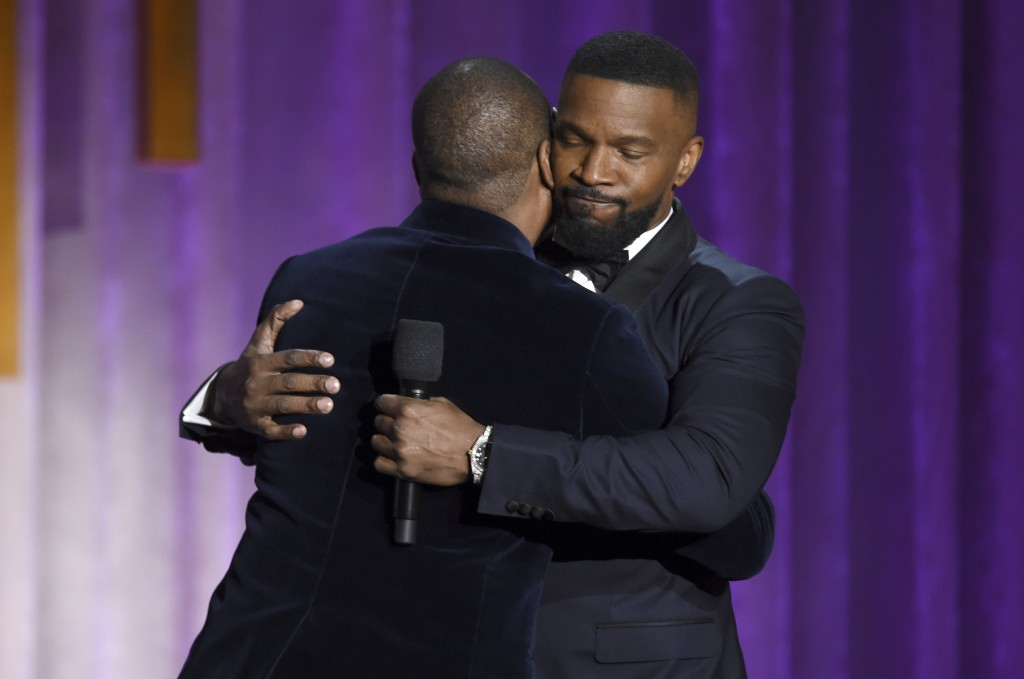 Eddie Murphy, left, and Jamie Foxx hug on stage at the Governors Awards on Sunday, Oct. 27, 2019, at the Dolby Ballroom in Los Angeles. (Photo by Chri...