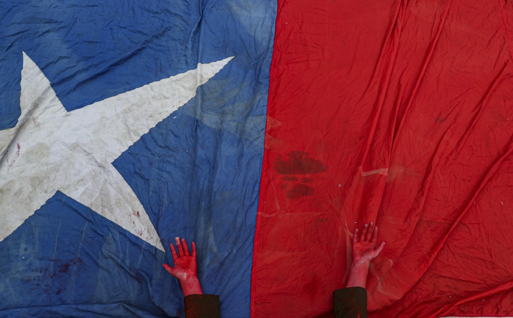 A performer places her hands, covered in red paint to symbolize blood, on a Chilean flag to honor protesters who have died amid days of demonstrations...