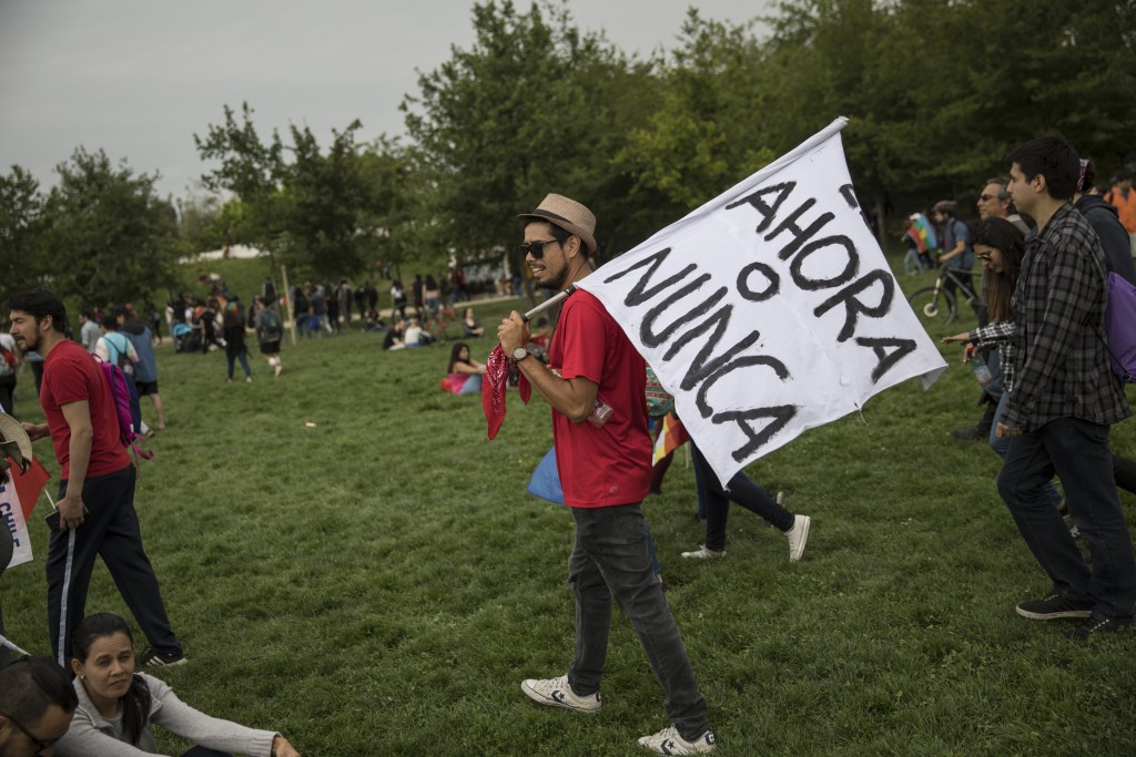 """A protester carries the Spanish message """"It's now or never"""" through O'Higgins Park during an anti-government music concert in Santiago, Chile, Sunday,..."""