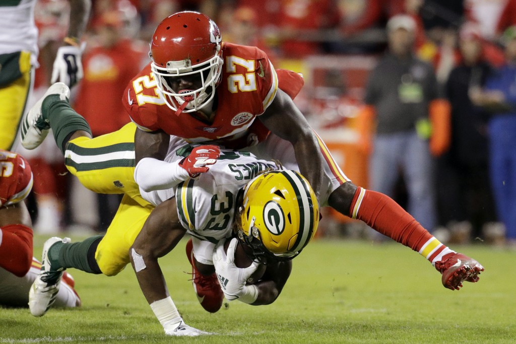 Green Bay Packers running back Aaron Jones (33) is tackled by Kansas City Chiefs cornerback Rashad Fenton (27) during the first half of an NFL footbal...