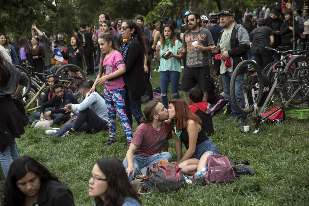 A couple kisses during an anti-government music concert in O'Higgins Park in Santiago, Chile, Sunday, Oct. 27, 2019. Days of demonstrations have been ...