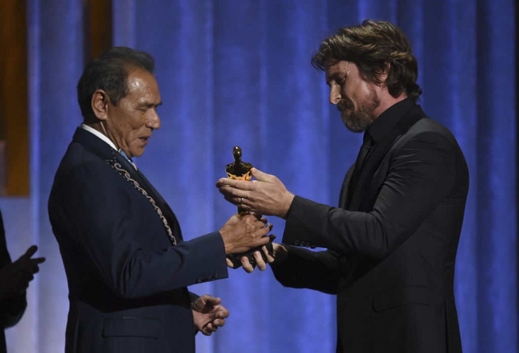 Christian Bale, right, presents an honorary award to Wes Studi at the Governors Awards on Sunday, Oct. 27, 2019, at the Dolby Ballroom in Los Angeles....