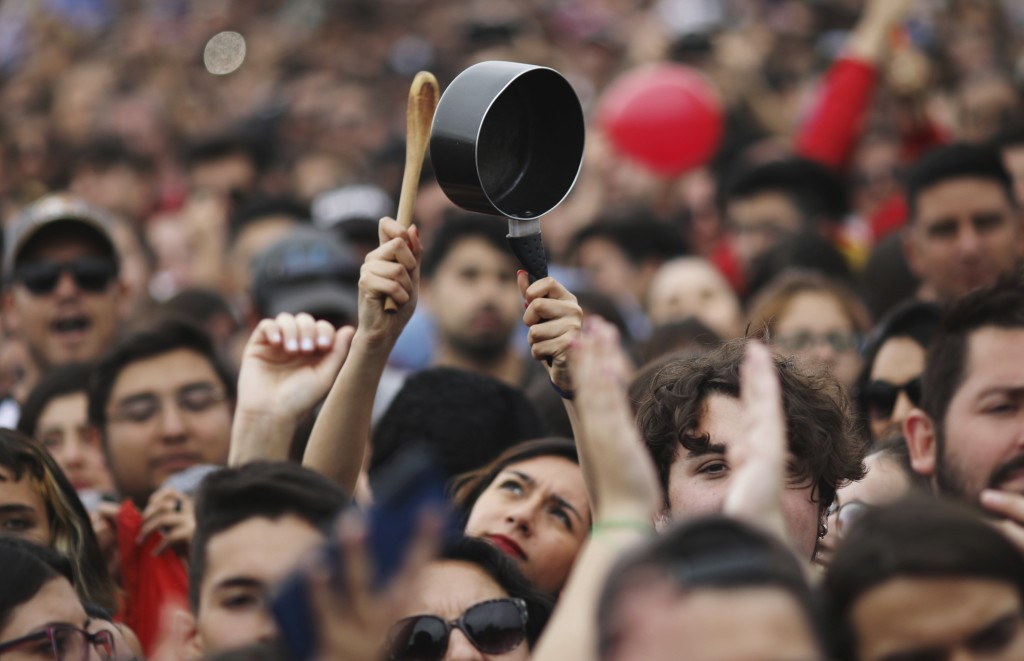 A woman bangs a pot, a sign of protest, during an anti-government music concert in O'Higgins Park in Santiago, Chile, Sunday, Oct. 27, 2019. Days of d...