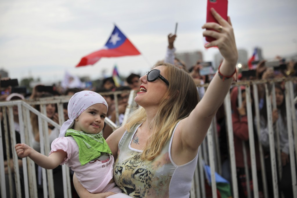 Veronica Gosgling sings with her two-year-old daughter Aurora and takes a selfie during an anti-government music concert in O'Higgins Park in Santiago...