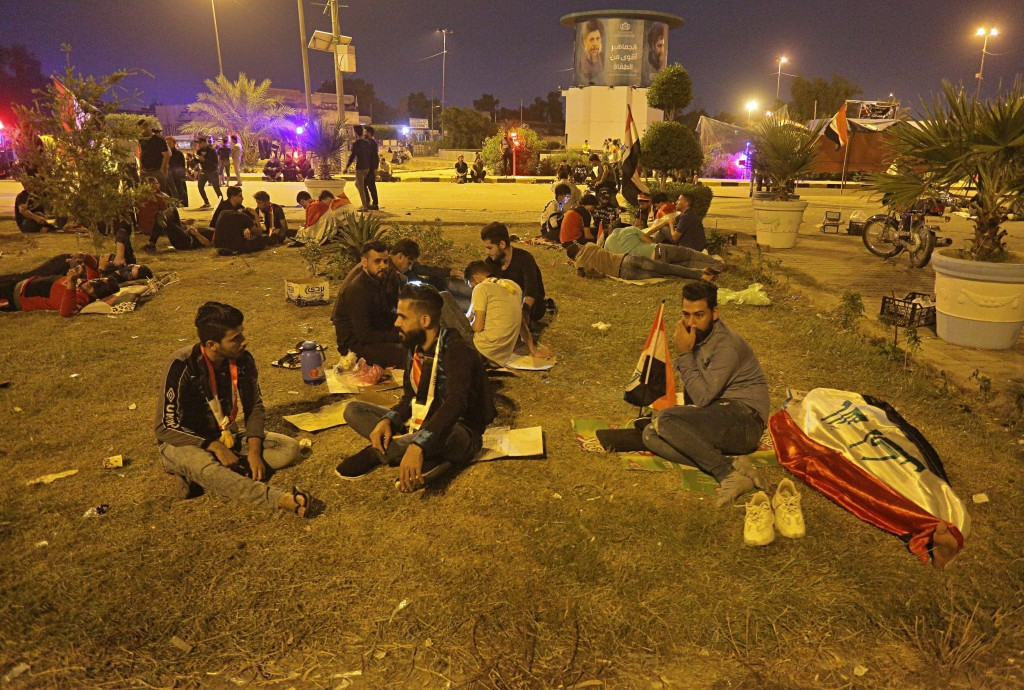 Anti-government protesters rest during a sit-in near the closed Najaf provincial council, Iraq, early Monday, Oct. 28, 2019. Protests have resumed in ...