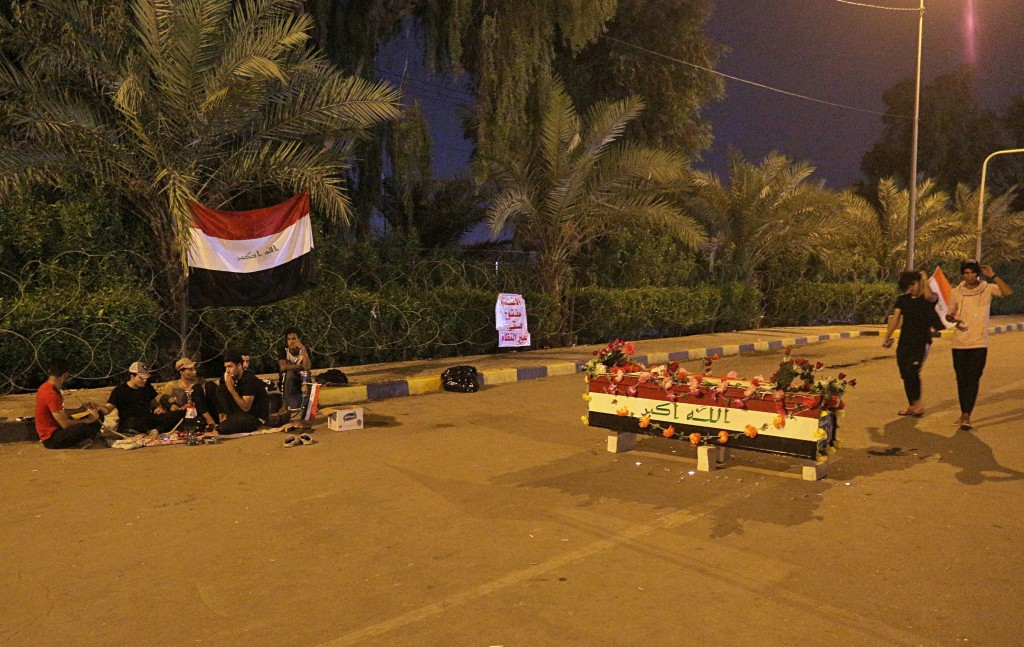Anti-government protesters rest near a symbolic coffin bearing the colors of the national flag during a sit-in near the closed Najaf provincial counci...