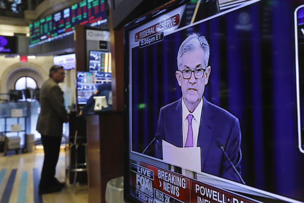 FILE - In this June 19, 2019, file photo the Washington news conference of Federal Reserve Chair Jerome Powell appears on television screen on the tra...