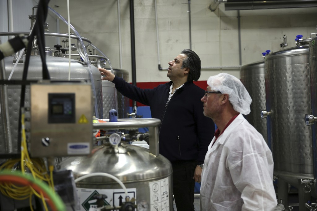 In this April 12, 2019 photo, Bruce Khabbazi, owner of the Persian Empire Distillery, center, instructs one of his employees as they prepare to fill '...