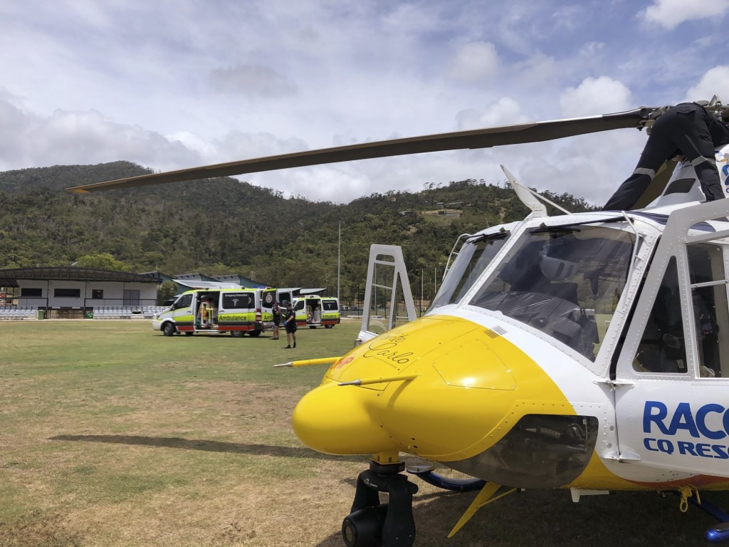 CORRECTS THE SOURCE - In this photo provided by RACQ CQ Rescue, a helicopter and ambulances used in the rescue of two tourists attacked by a shark are...