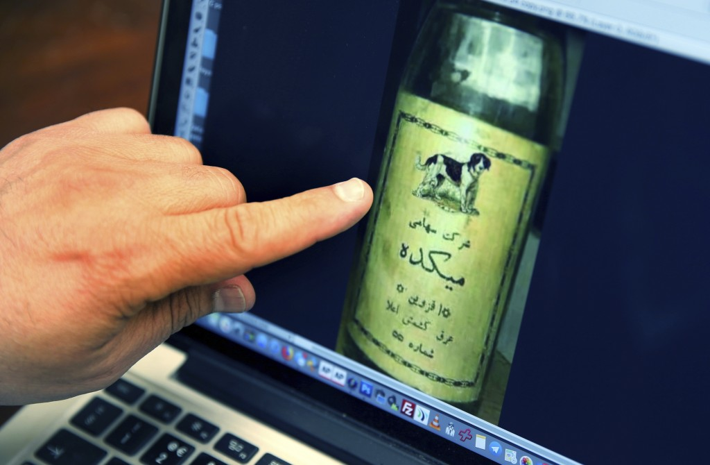 In this April 12, 2019 photo, Bruce Khabbazi, owner of the Persian Empire Distillery, points to an image of a dog on a photo of an original bottle of ...