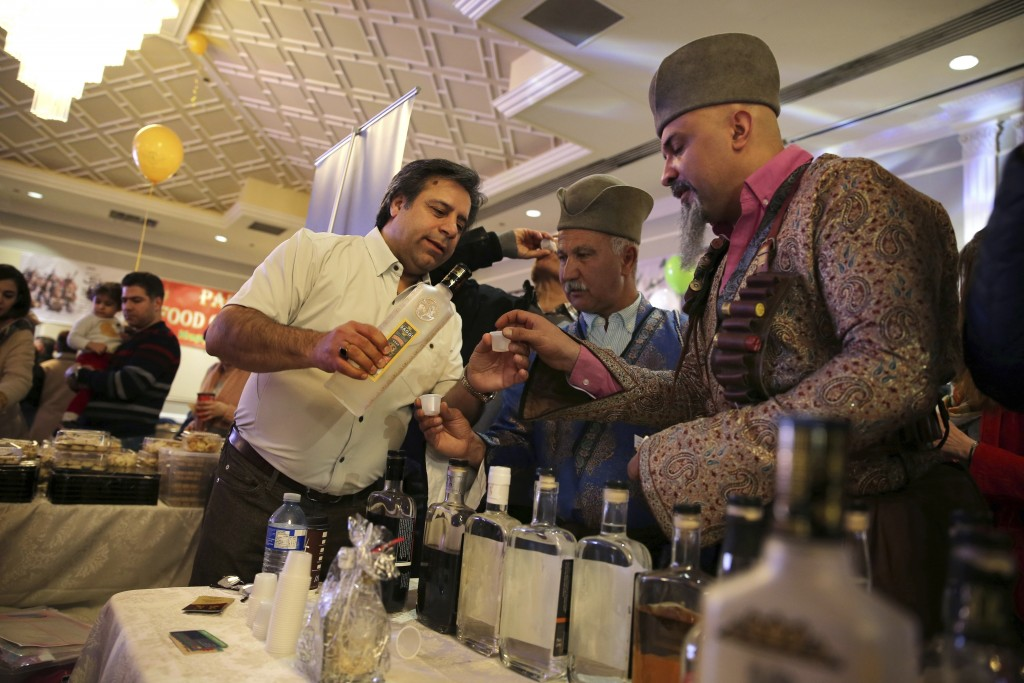 In this March 16, 2019 photo, Bruce Khabbazi, the owner of the Persian Empire Distillery, center left, serves 'Arak Saggi' to a man in a traditional I...