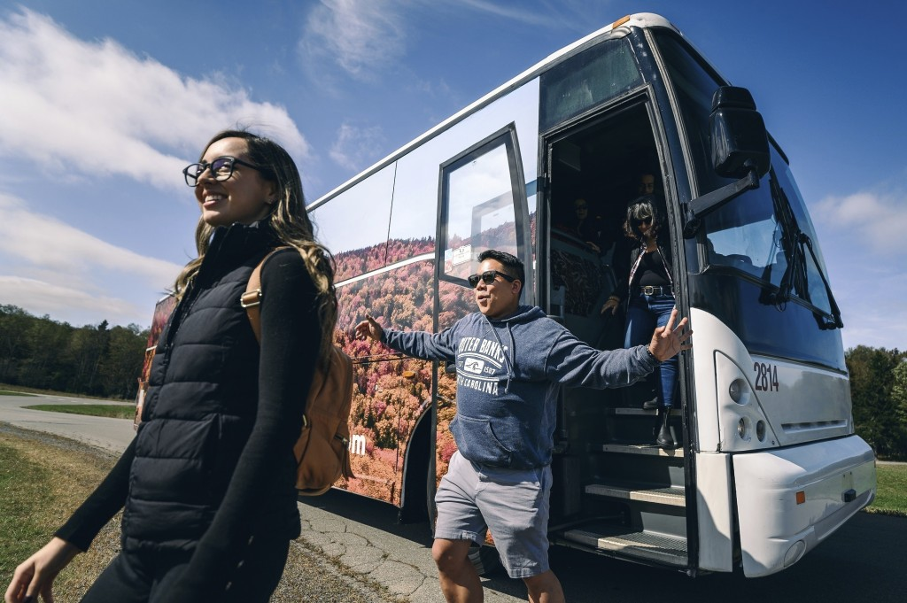This Oct. 5, 2019 photo released by West Virginia Division of Tourism shows Maria Bedolla, left, and Alfred Ting stepping off a tour bus that arrived ...