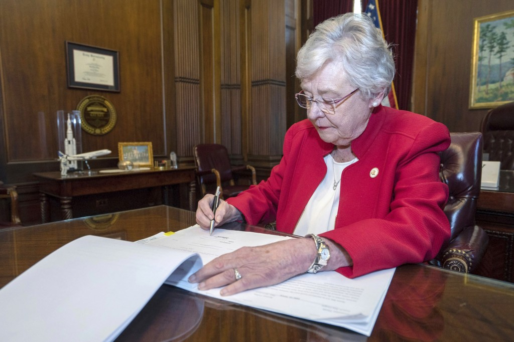 FILE-In this Wednesday, May 15, 2019 file photo released by the state shows Alabama Gov. Kay Ivey signing a bill that virtually outlaws abortion in th...