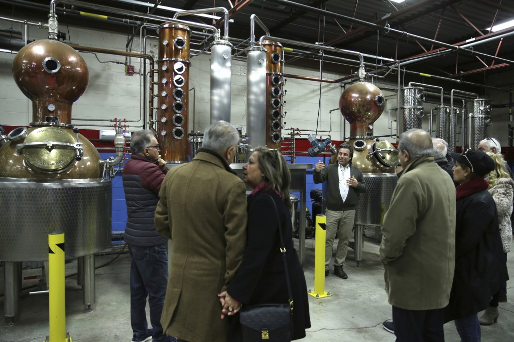 In this March 25, 2019 photo, Bruce Khabbazi, owner of the Persian Empire Distillery, talks about his business with a group of visitors, at the distil...