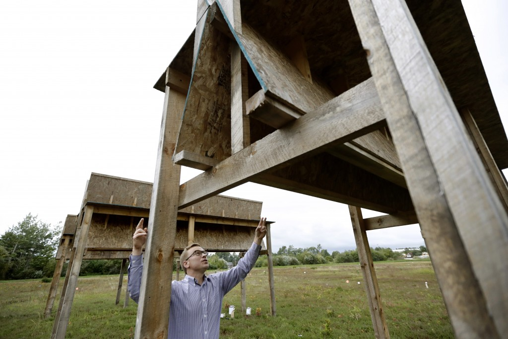 In this Wednesday, Oct. 2, 2019, photo, Adam Schumaker, vice president of development for NextSun Energy, examines a wooden replica of an agricultural...