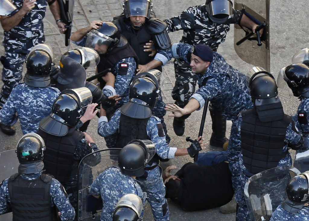 A riot police officer, center right, stops other policemen from beating a protester who lies on the ground, after clashes erupted between an anti-gove...