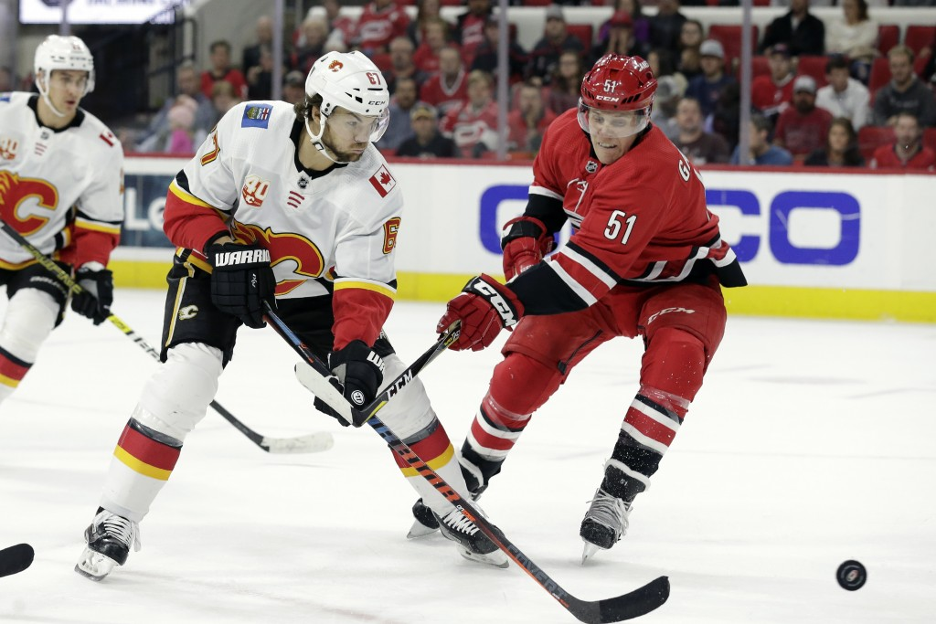 Calgary Flames right wing Michael Frolik (67), of the Czech Republic, and Carolina Hurricanes defenseman Jake Gardiner (51) chase the puck during the ...