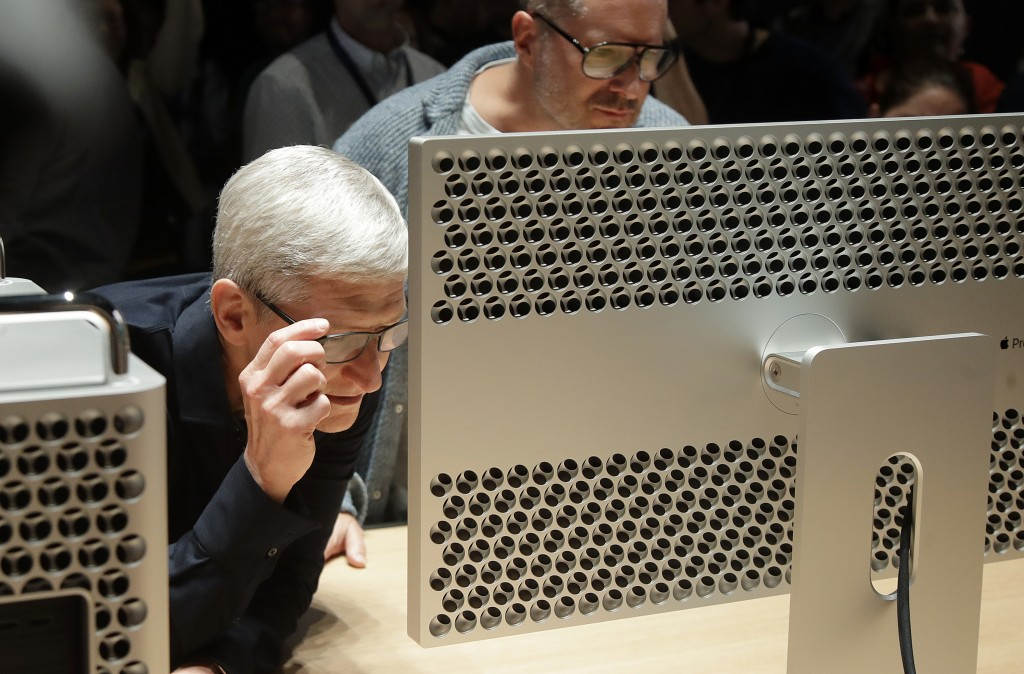 FILE - In this June 3, 2019, file photo Apple CEO Tim Cook, left, and chief design officer Jonathan Ive look at a Mac Pro in the display room at the A...