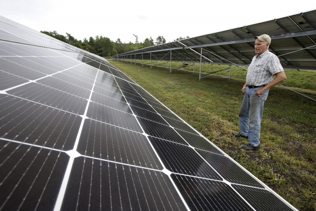 In this Wednesday, Oct. 2, 2019 photo cranberry grower Dick Ward, of Carver, Mass., stands near a solar array in a cranberry bog on his farm, in Carve...