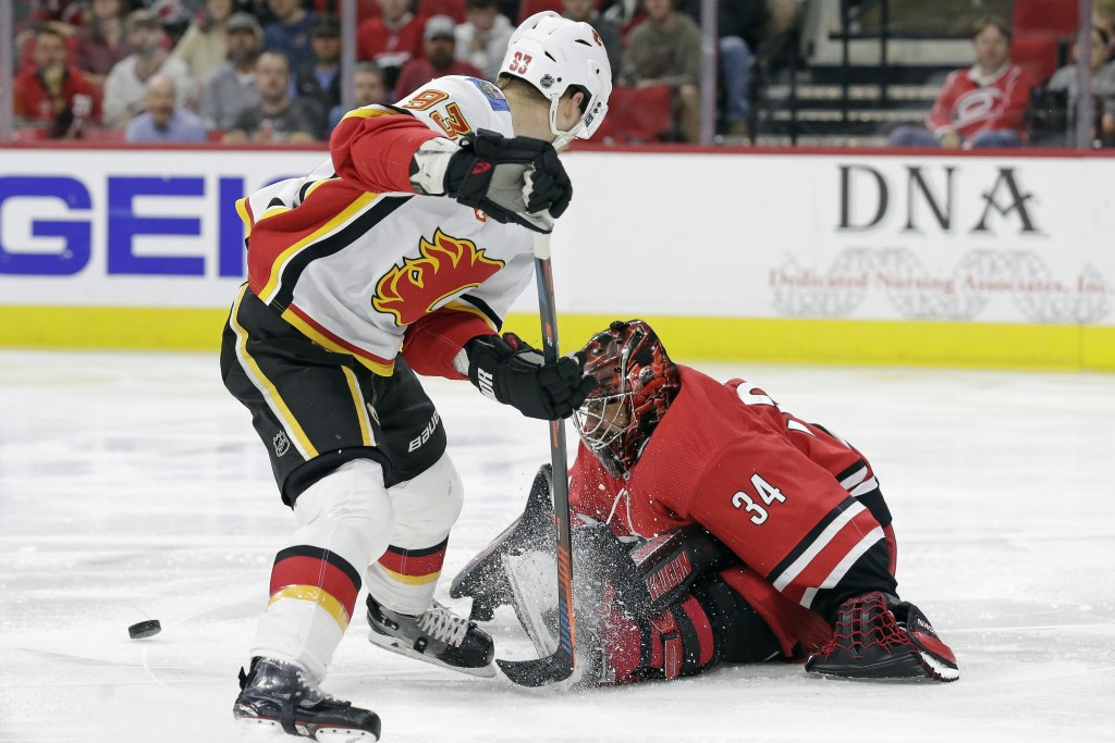 Carolina Hurricanes goaltender Petr Mrazek (34), of the Czech Republic, blocks Calgary Flames center Sam Bennett (93) during the first period of an NH...