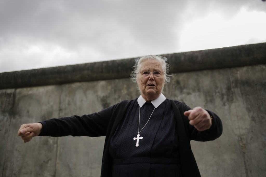 In this Sept. 18, 2019, photo, Sister Brigitte Queisser of the Lutheran Lazarus Order talks in front of concrete remains of the Berlin Wall during an ...