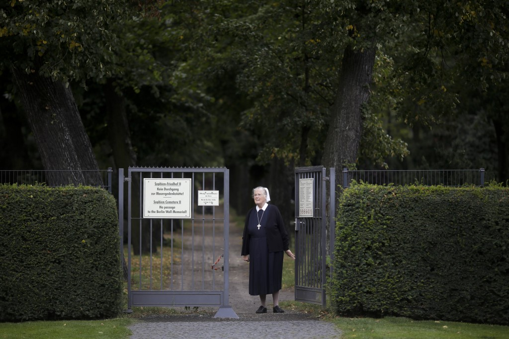 In this Sept. 18, 2019, photo, Sister Brigitte Queisser of the Lutheran Lazarus Order poses at the entrance of a cemetery that used to be behind the B...