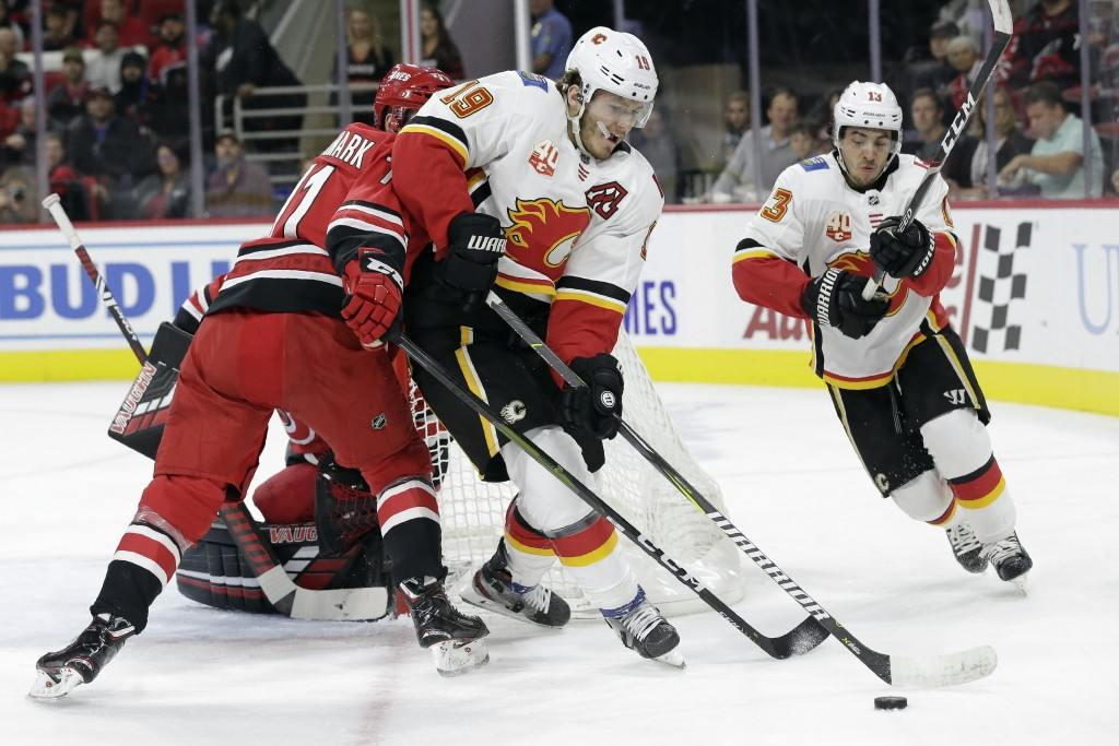 Calgary Flames' Matthew Tkachuk (19) and Johnny Gaudreau (13) chase the puck with Carolina Hurricanes center Lucas Wallmark (71), of Sweden, during th...