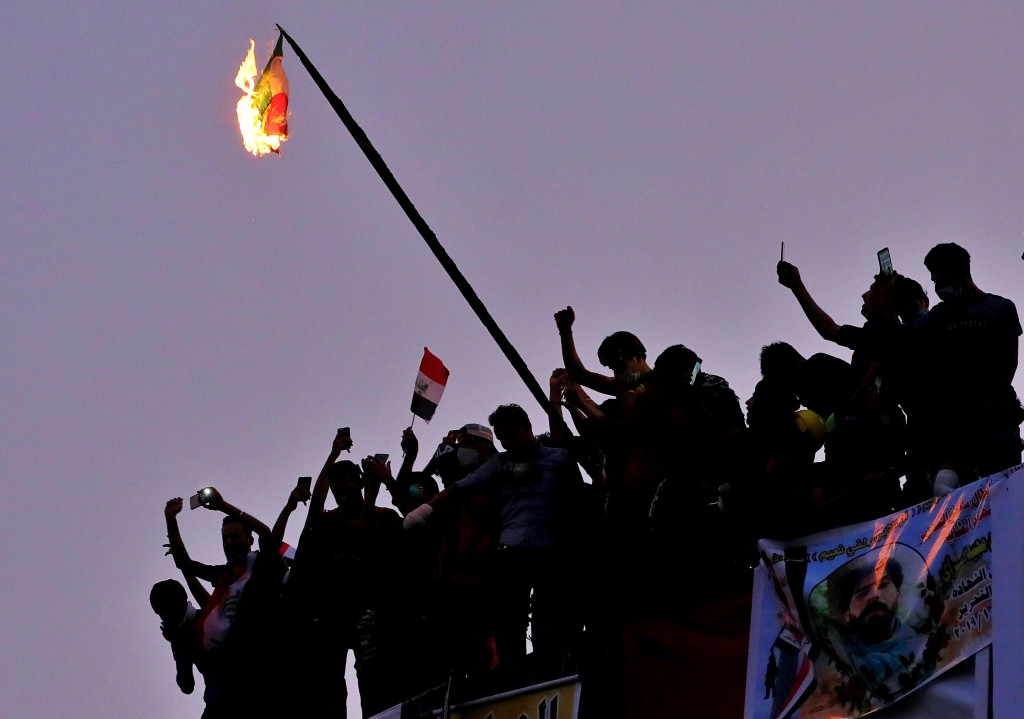 Iraqi anti-government protesters burn the Iranian flag during a demonstration in Baghdad, Iraq, Tuesday, Oct. 29, 2019. (AP Photo/Hadi Mizban)