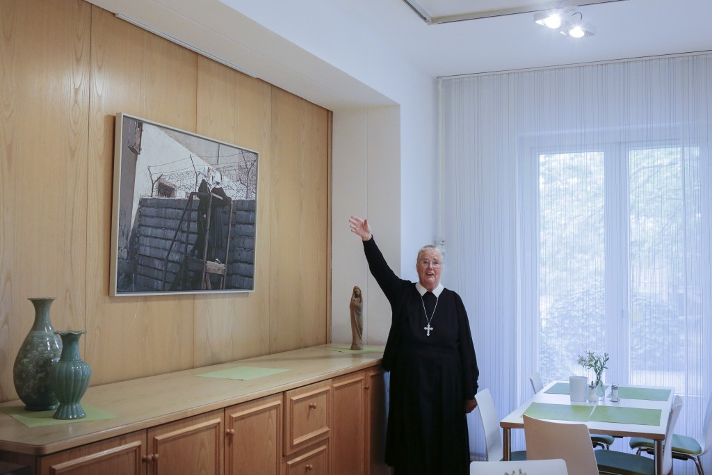 In this Sept. 18, 2019, photo, Sister Brigitte Queisser of the Lutheran Lazarus Order shows a historic photo of the Lazarus sisters looking over the B...