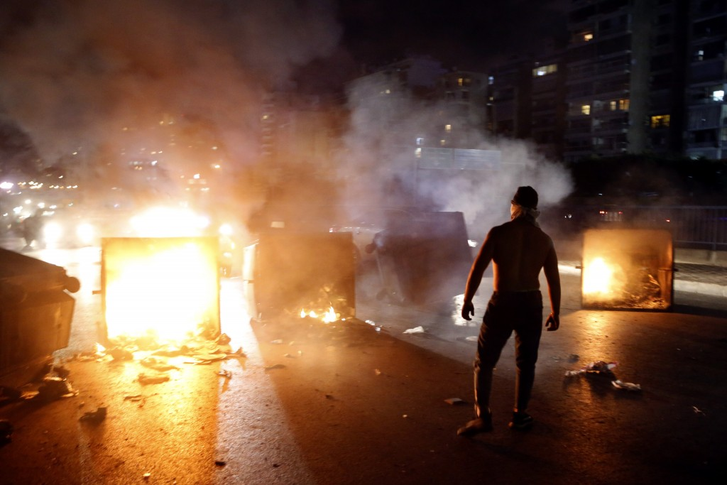 A supporter of Lebanese Prime Minister Saad Hariri burns garbage containers to block  a main road, in Beirut, Lebanon, Tuesday, Oct. 29, 2019. Hariri ...