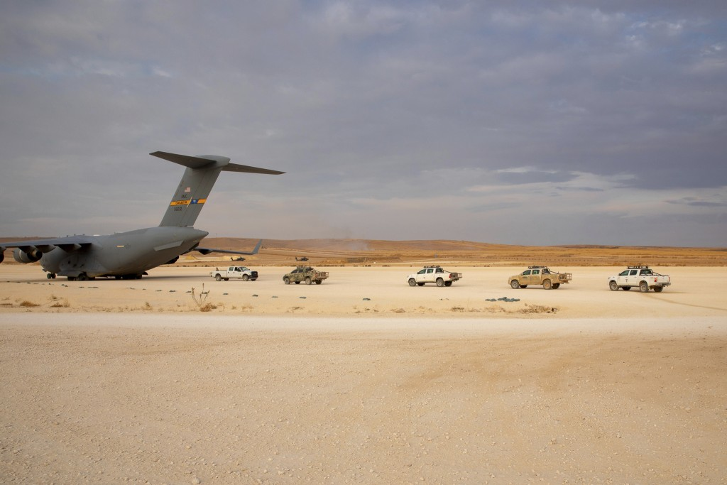In this Oct. 25, 2019, photo, released by the U.S. Army Reserve, pickup trucks are vehicles lined up to be loaded onto a cargo plane as part of the de...