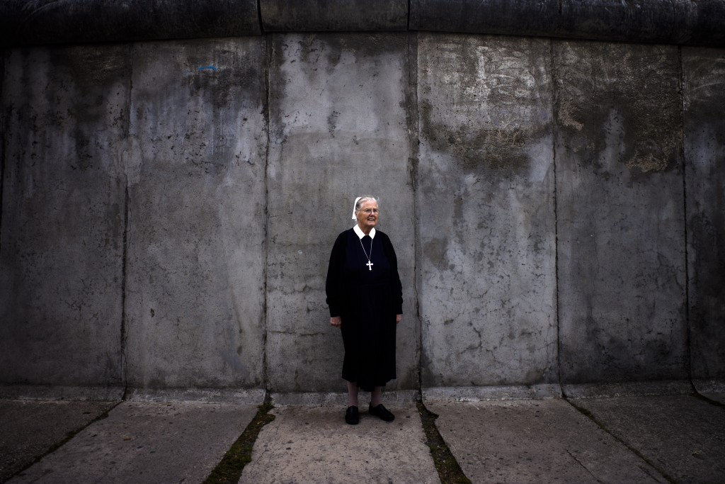 In this Sept. 18, 2019, photo, Sister Brigitte Queisser of the Lutheran Lazarus Order poses for a photo in front of concrete remains of the Berlin Wal...