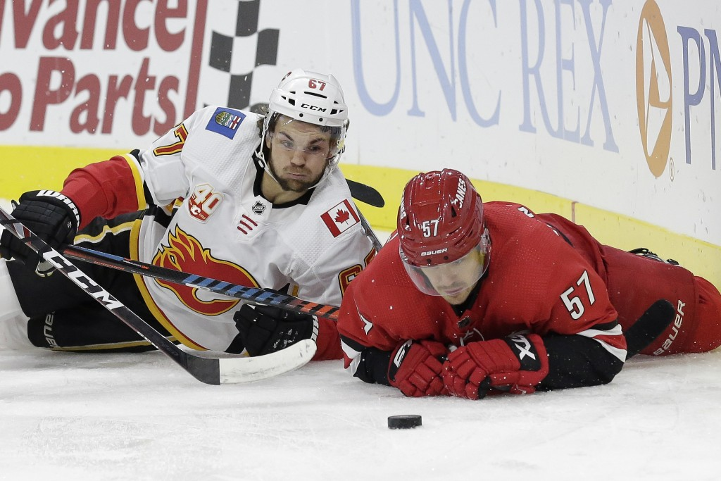 Carolina Hurricanes defenseman Trevor van Riemsdyk (57) and Calgary Flames right wing Michael Frolik (67) fall to the ice while chasing the puck durin...