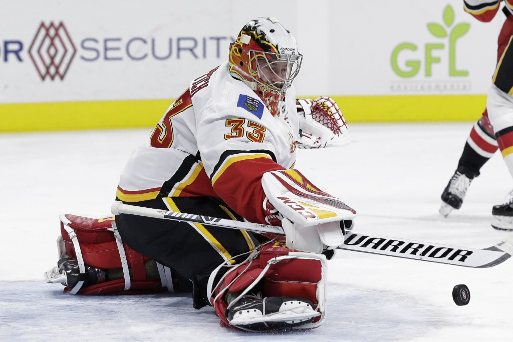Calgary Flames goaltender David Rittich (33) deflects a shot during the second period of the team's NHL hockey game against the Carolina Hurricanes in...