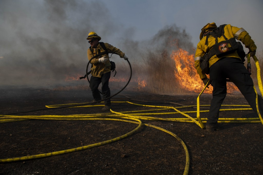 Firefighters work to prevent flames from reaching nearby homes during the Easy Fire, Wednesday, Oct. 30, 2019, in Simi Valley, Calif. The fire has che...