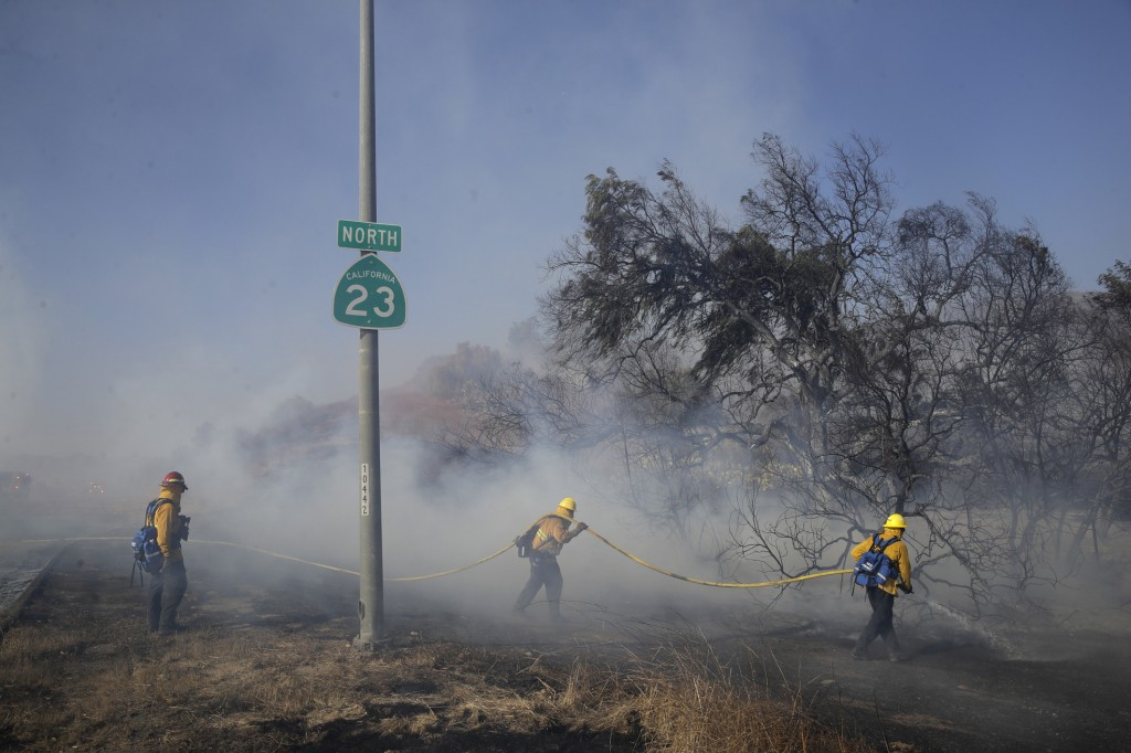 Firefighters put out hot spots along Highway 23, closed to traffic due to the Easy Fire, Wednesday, Oct. 30, 2019, in Simi Valley, Calif. (AP Photo/Ma...