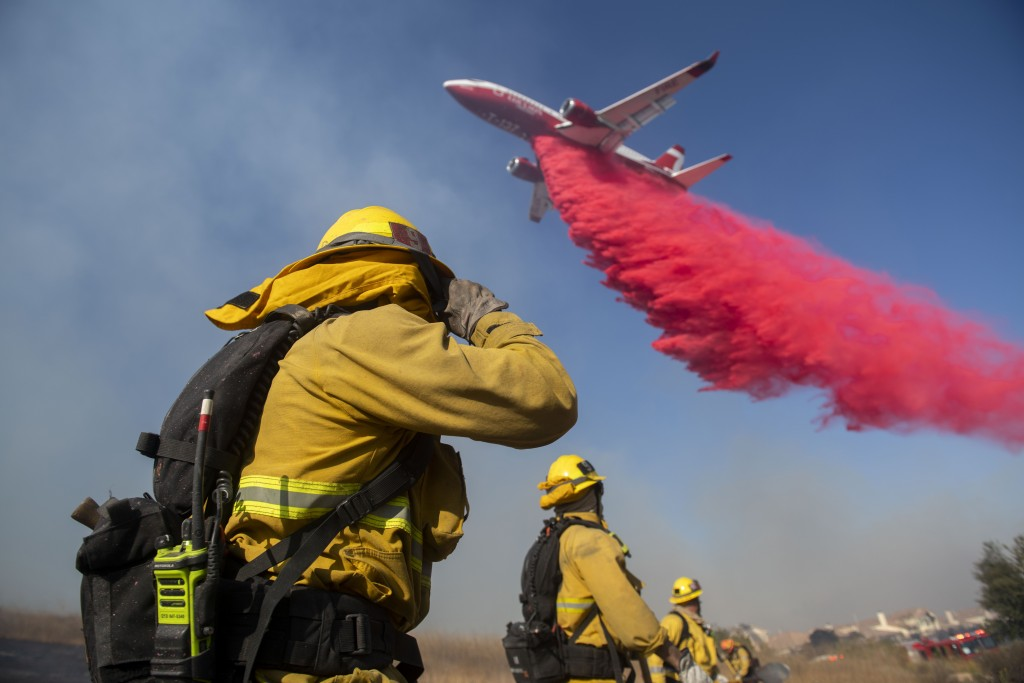 Firefighters brace themselves for incoming fire retardant during the Easy Fire, Wednesday, Oct. 30, 2019, in Simi Valley, Calif. Fire officials say th...