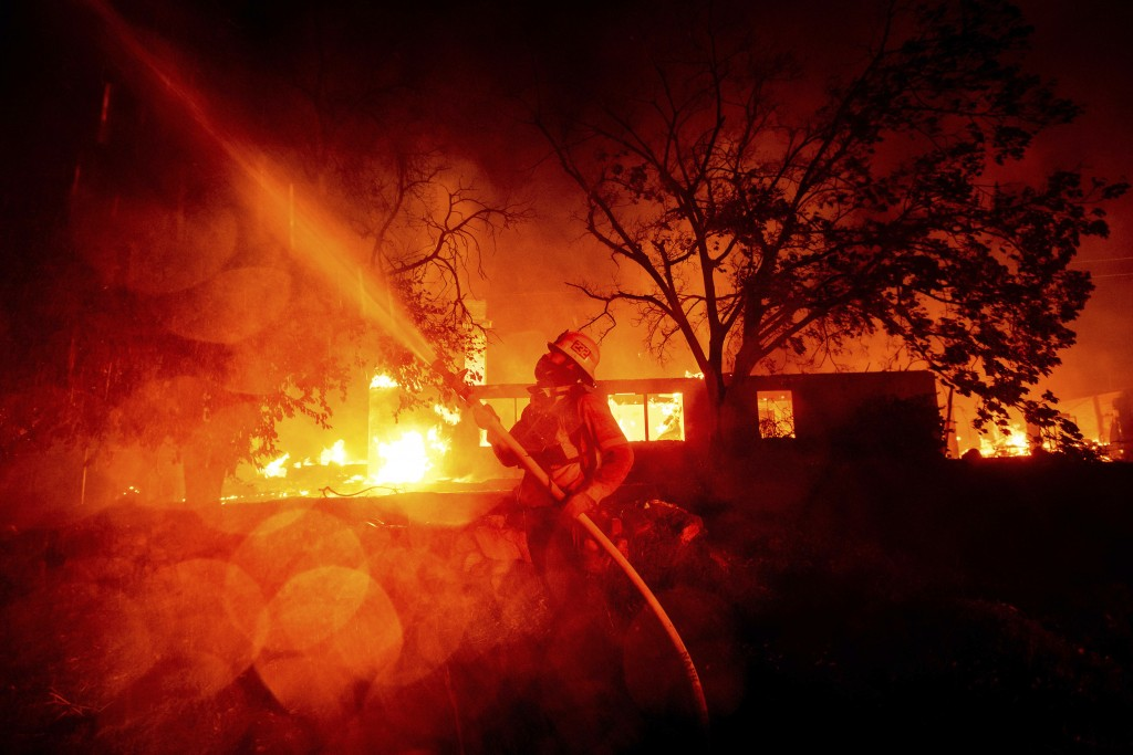 A firefighter sprays water as flames from the Hillside fire consume a residence in San Bernardino, Calif., on Thursday, Oct. 31, 2019. The blaze, whic...