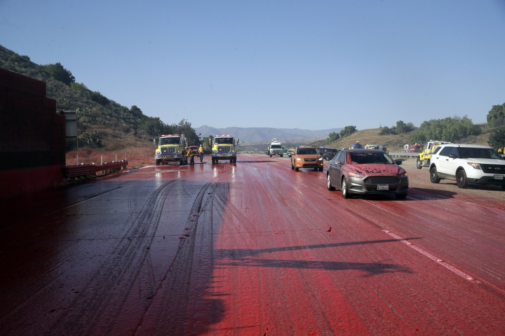 Highway 23 is covered in fire retardant after an air tanker drop as the Easy Fire threatened to jump the highway Wednesday, Oct. 30, 2019, in Simi Val...