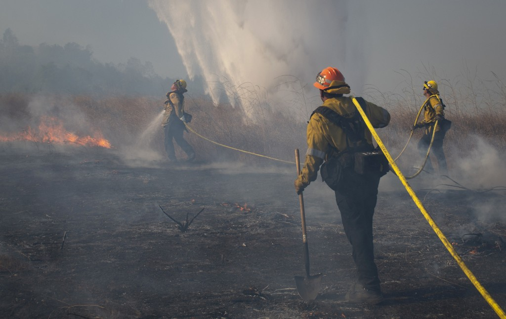 Firefighters work to prevent flames from reaching nearby homes as a helicopter drops water during the Easy Fire, Wednesday, Oct. 30, 2019, in Simi Val...