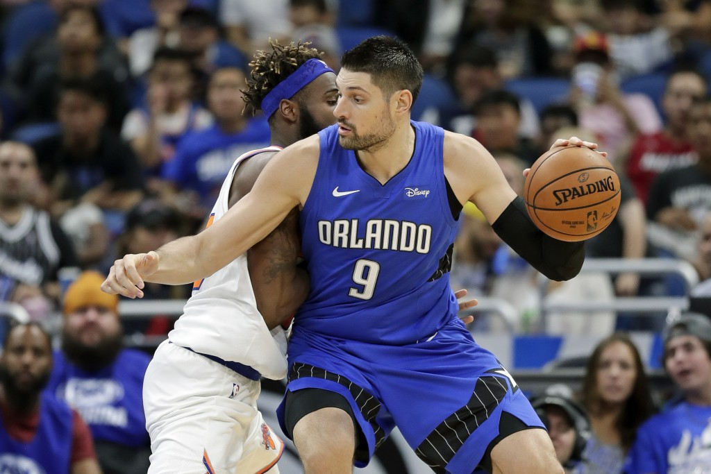 Orlando Magic center Nikola Vucevic (9) makes a move to get around New York Knicks' Mitchell Robinson, left, during the first half of an NBA basketbal...