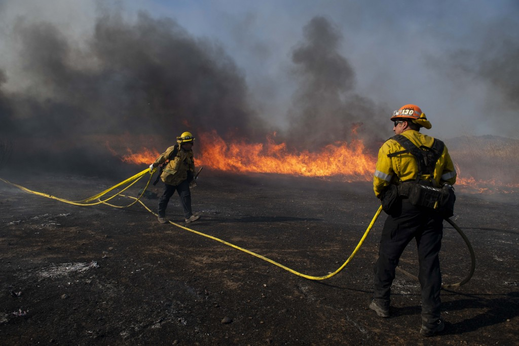 Firefighters work to prevent flames from reaching nearby homes while battling the Easy Fire, Wednesday, Oct. 30, 2019, in Simi Valley, Calif.  It has ...