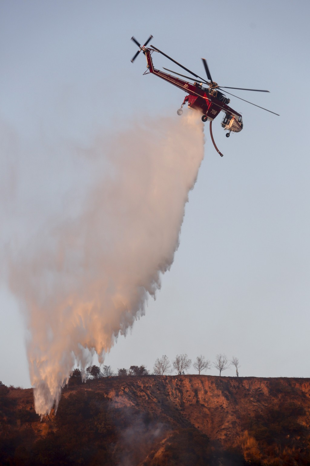 A helicopter drops water to put out hotspots in Simi Valley, Calif., Wednesday, Oct. 30, 2019. California is under siege at both ends of the state fro...