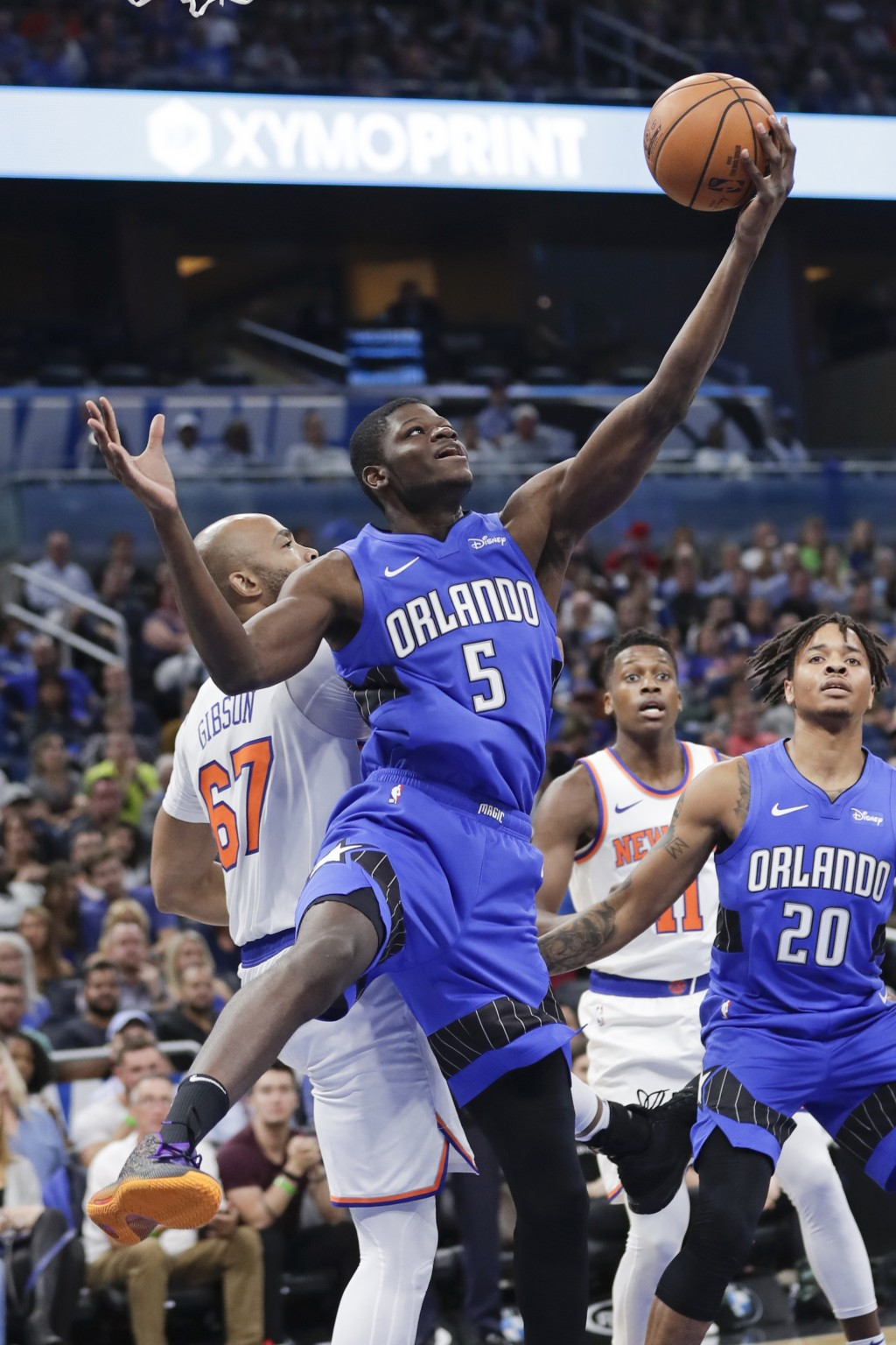 Orlando Magic's Mo Bamba (5) grabs a rebound in front of New York Knicks' Taj Gibson (67) as Markelle Fultz (20) looks on during the first half of an ...