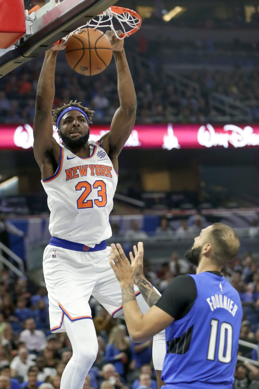 New York Knicks' Mitchell Robinson (23) dunks the ball over Orlando Magic's Evan Fournier (10) during the first half of an NBA basketball game, Wednes...