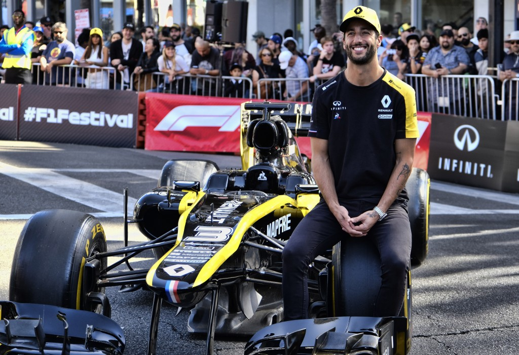 Renault F1 Team driver Daniel Ricciardo sits on a tire of his car along Hollywood Boulevard in the Hollywood section of Los Angeles on Wednesday, Oct....