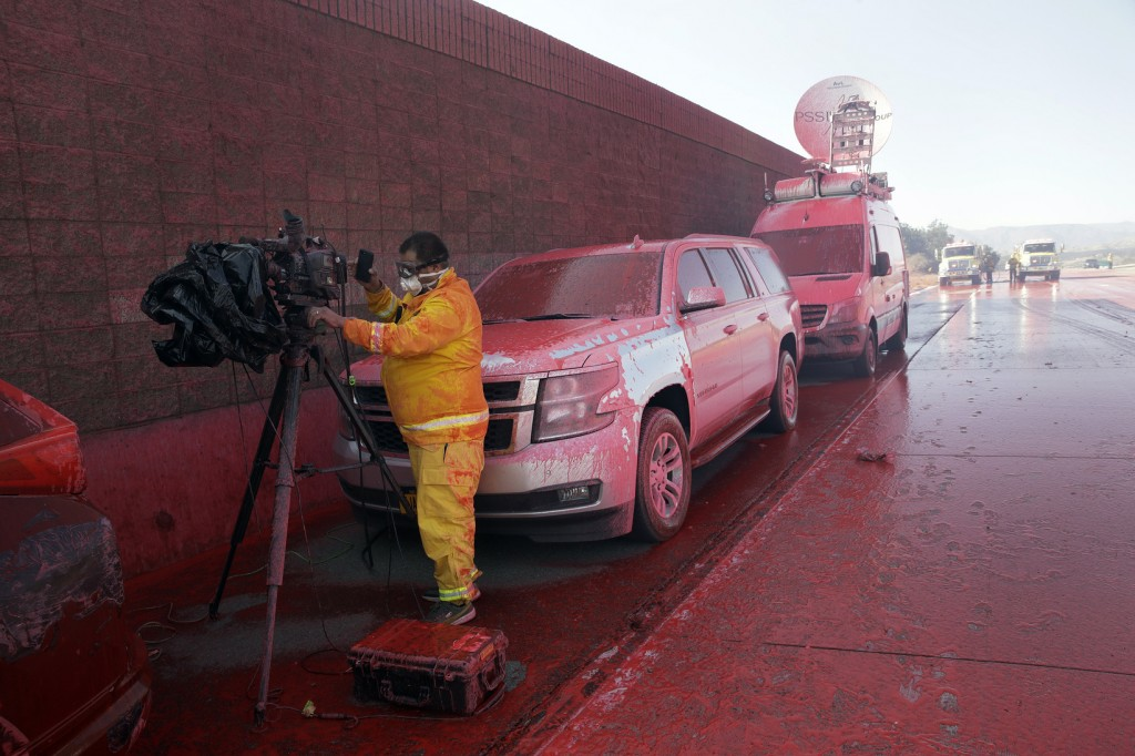 News crews and their vehicles are covered with fire retardant after an air tanker drop on Highway 23 as fire crews work the Easy Fire, Wednesday, Oct....