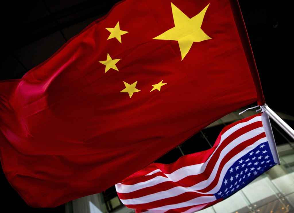 In this Nov. 7, 2012 photo, U.S. and Chinese national flags are hung outside a hotel during the U.S. Presidential election event, organized by the U.S...