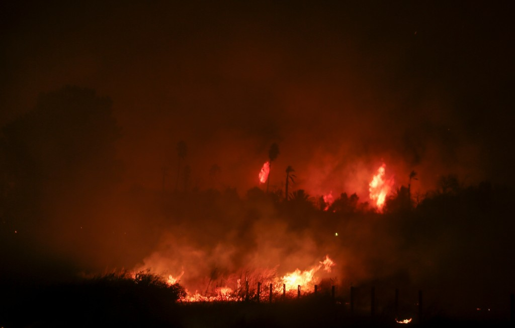 A wildfire burns in Riverside, Calif. Thursday, Oct. 31, 2019. Santa Ana winds are expected to linger for a final day after driving more than a dozen ...